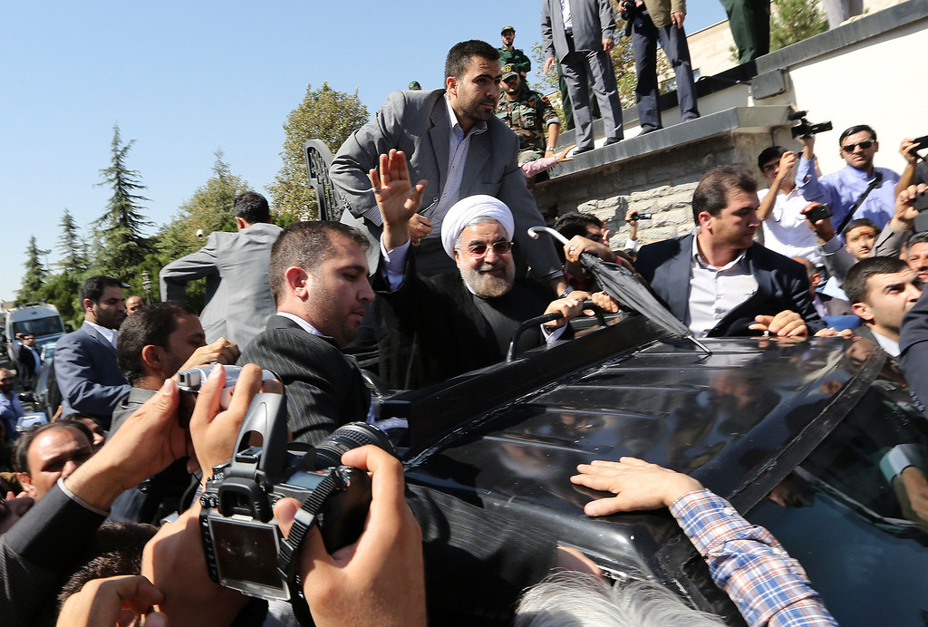 Description of . Iranian president Hassan Rouhani waves to supporters as his motorcade leaves Tehran's Mehrabad Airport upon his arrival from New York, on September 28, 2013. Hardline Islamists chanted