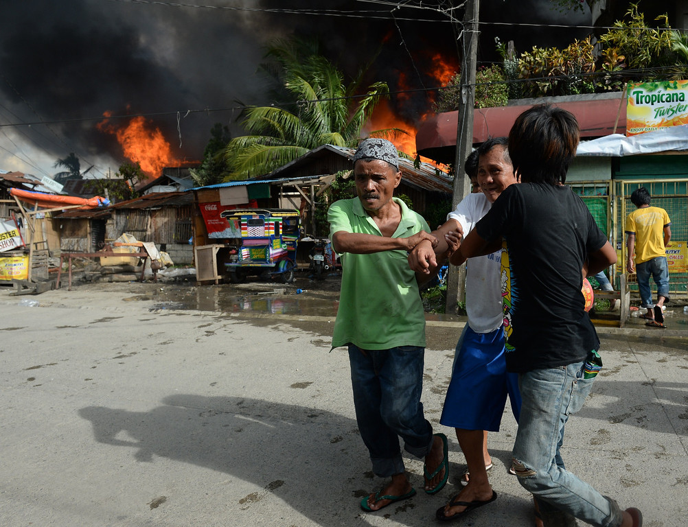 Description of . A sick resident is evacuated from burning houses during a fire fight between government forces and Muslim rebels as stand-off entered its fourth day in Zamboanga City on the southern island of Mindanao on September 12, 2013. .  AFP PHOTO/TED ALJIBE/AFP/Getty Images