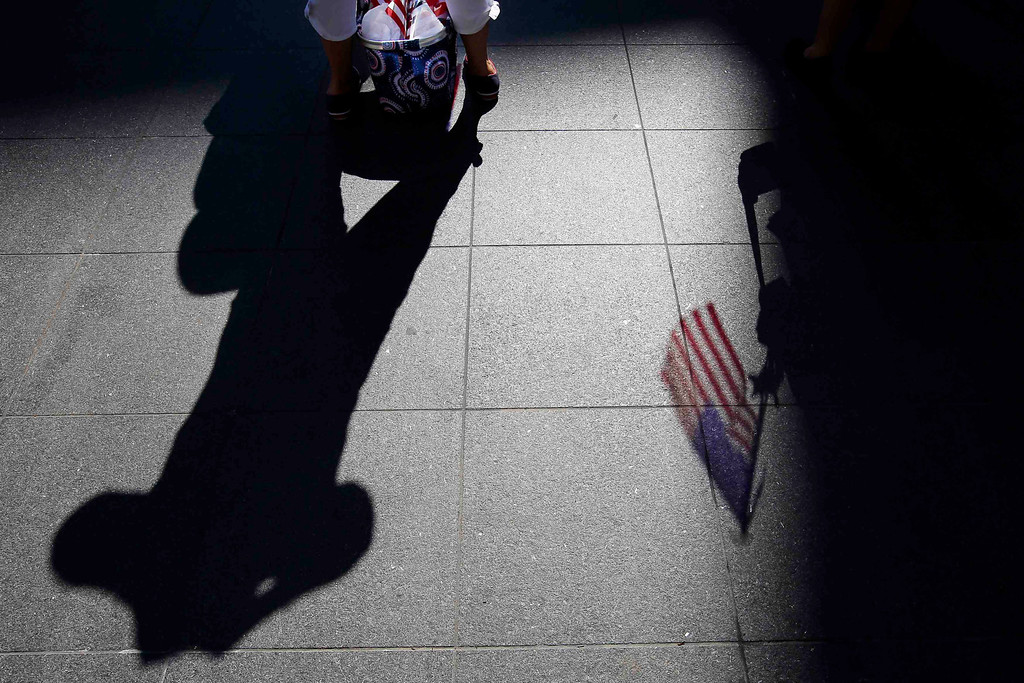 Description of . A United States flag casts a shadow on the ground as spectators wait for a public reading the United States Declaration of Independence, part of Fourth of July Independence Day celebrations, in Boston, Massachusetts July 4, 2013. People across the United States gathered on Thursday for parades, picnics and fireworks at Independence Day celebrations, held under unprecedented security following the Boston Marathon bombings. Spectators waving U.S. flags and wearing red, white and blue headed for public gatherings in Boston, New York, Washington, Atlanta and other cities under the close watch of police armed with hand-held chemical detectors, radiation scanners and camera surveillance, precautions sparked by the deadly April 15 bombings.    REUTERS/Brian Snyder
