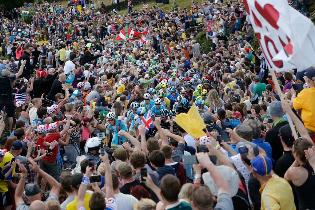 Description of . Thousands of spectators line the roads as the pack climbs Bradfield pass during the second stage of the Tour de France cycling race over 201 kilometers (124.9 miles) with start in York and finish in Sheffield, England, Sunday, July 6, 2014. (AP Photo/Christophe Ena)