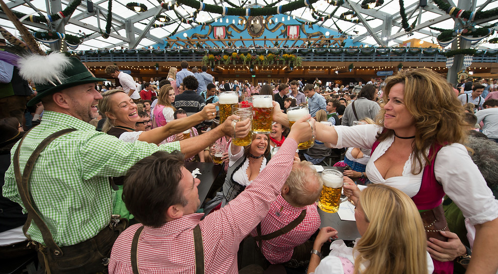 Description of . Visitors in Bavarian style clothes raise their glasses after getting their first Oktoberfest beer in the Schottenhamel-tent at the Oktoberfest 2013 beer festival at Theresienwiese on September 21, 2013 in Munich, Germany. Shortly before Munich mayor Christian Ude (SPD) had tapped the first barrel with the traditional