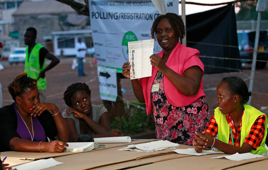 Description of . An official from the Independent Electoral and Boundaries Commission (IEBC) holds up a ballot paper as they count after voting close for presidential and parliamentary elections in Kisumu, 350 km (218 miles) west of the capital Nairobi, March 4, 2013. REUTERS/Thomas Mukoya