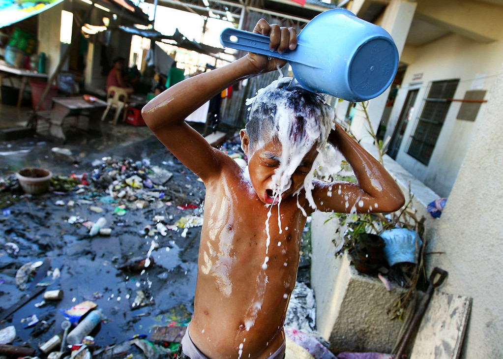 Description of . A young Filipino takes a shower at a school turned into a temporary shelter for those affected by Typhoon Haiyan, in Tacloban, Philippines, Monday, Nov. 18, 2013. Hundreds of thousands of people were displaced by Typhoon Haiyan, which tore across several islands in the eastern Philippines on Nov. 8. (AP Photo/Dita Alangkara)
