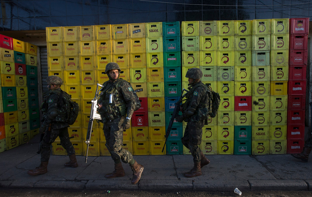 Description of . Army soldiers walk beside beer crates during an operation to occupy the Mare slum complex in Rio de Janeiro, Brazil, Saturday, April 5, 2014. More than 2,000 Brazilian Army soldiers moved into the Mare slum complex early Saturday in a bid to improve security and drive out the heavily armed drug gangs that have ruled the sprawling slum for decades. (AP Photo/Silvia Izquierdo)