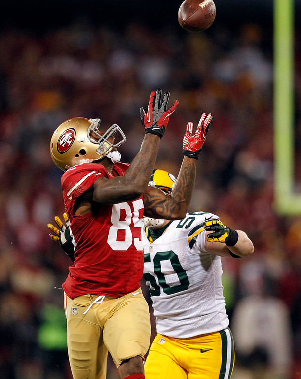 Description of . San Francisco 49ers tight end Vernon Davis (85) catches a pass over Green Bay Packers inside linebacker A.J. Hawk (50) during the third quarter of an NFC divisional playoff NFL football game in San Francisco, Saturday, Jan. 12, 2013. (AP Photo/Tony Avelar)