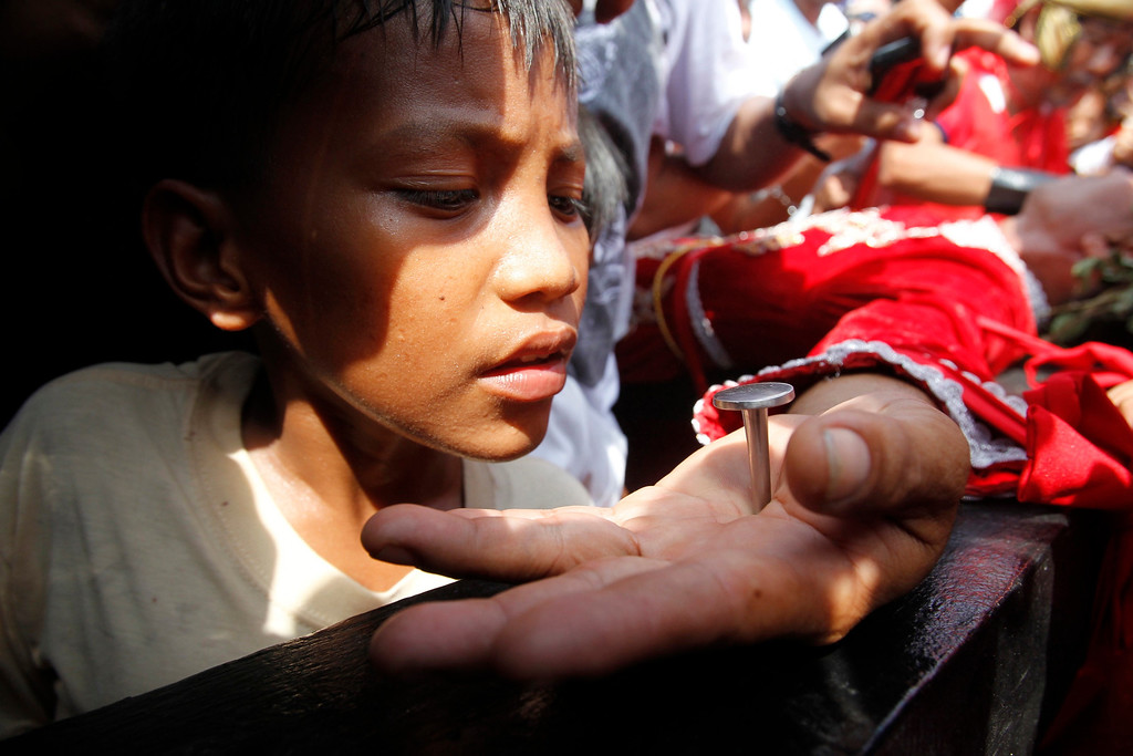 Description of . A boy looks at the palm of a penitent nailed on a wooden cross during a reenactment of Jesus Christ's crucifixion on Good Friday in Barangay Cutud, San Fernando, Pampanga in northern Philippines April 6, 2012. REUTERS/Erik De Castro