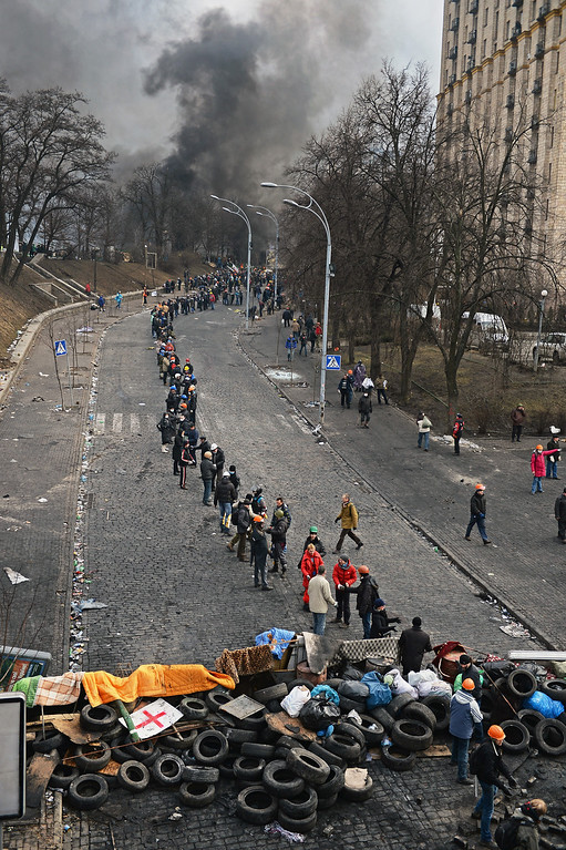 Description of . Anti-government protesters form a human chain as they carry rocks and tyres to rebuild barricades following continued clashes with police in Independence square, despite a truce agreed between the Ukrainian president and opposition leaders on February 20, 2014 in Kiev, Ukraine. After several weeks of calm, violence has again flared between police and anti-government protesters, who are calling to oust President Viktor Yanukovych over corruption and an abandoned trade agreement with the European Union  (Photo by Jeff J Mitchell/Getty Images)