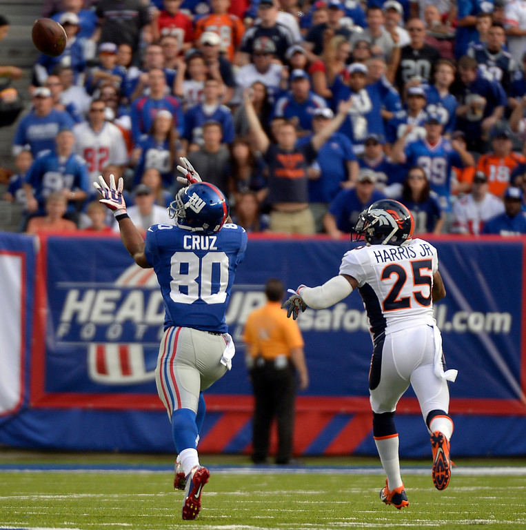 Description of . Wide receiver Victor Cruz (80) of the New York Giants catches a long pass from quarterback Eli Manning (10) of the New York Giants as cornerback Chris Harris (25) of the Denver Broncos defends on the play during the first quarter September 15, 2013 MetLIFE Stadium. (Photo by John Leyba/The Denver Post)