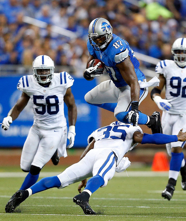 Description of . Detroit Lions tight end Brandon Pettigrew (87) leaps over Indianapolis Colts strong safety Joe Lefeged (35) during the second quarter of an NFL football game at Ford Field in Detroit, Sunday, Dec. 2, 2012. (AP Photo/Rick Osentoski)