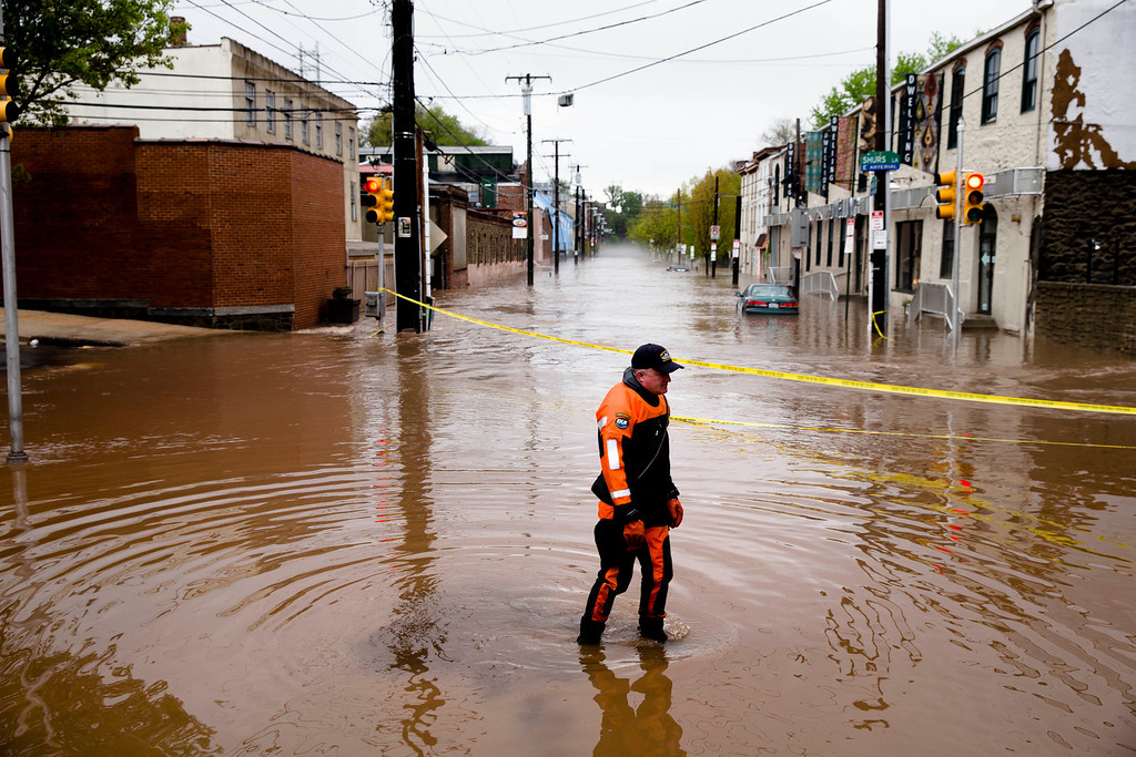 Description of . In this May 1, 2014 file photo, Marine unit police officer Robert Jonah walks through flood waters from the Schuylkill River on Main Street, Thursday, May 1, 2014, in the Manayunk neighborhood of Philadelphia.  (AP Photo/Matt Rourke)