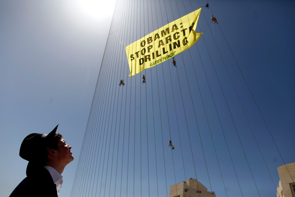 Description of . Greenpeace activists hang a banner saying 'Obama Stop Arctic drilling' on the cables of Jerusalem's Chords Bridge on March 21, 2013 in Jerusalem, Israel.  (Photo by Lior Mizrahi/Getty Images)