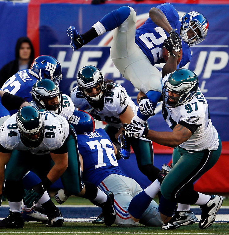 Description of . New York Giants\' David Wilson, top right, is upended by Philadelphia Eagles\' Cullen Jenkins (97) on the goal line during the first half of their NFL football game, Sunday, Dec. 30, 2012, in East Rutherford, N.J. The Giants won 42-7. (AP Photo/The Philadelphia Inquirer, Ron Cortes)
