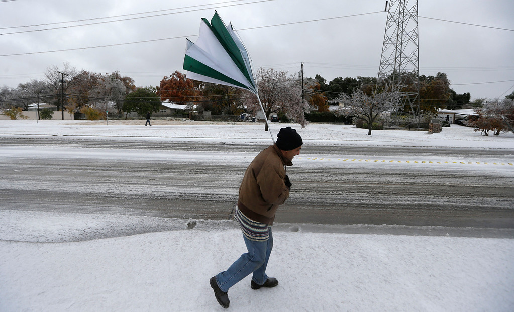 Description of . A gust of wind collapses Joseph Mezo's umbrella as he walks to work in light sleet  and ice conditions Friday morning, Dec. 6, 2013, in Dallas.   (AP Photo/LM Otero)