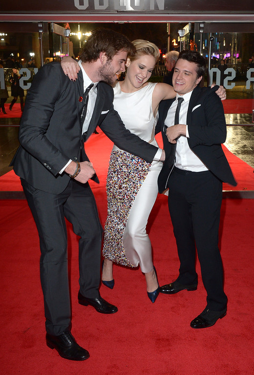 Description of . Actors Liam Hemsworth, left, Jennifer Lawrence and Josh Hutcherson share a joke on the red carpet as they arrive for the World Premiere of 'The Hunger Games: Catching Fire', on Monday Nov. 11, 2013, in Leicester Square, London. 'Catching Fire' is the second installment in 'The Hunger Games' trilogy. (Photo by Jon Furniss/Invision/AP)