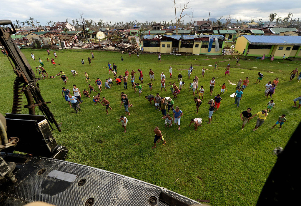 Description of . Villagers rush to retrieve relief aid delivered by a Huey helicopter from the Philippines Air Force in a village near Tacloban on November 17, 2013. Grieving survivors of a monster typhoon in the mainly Catholic Philippines flocked to shattered churches on November 17, listening to soothing sermons and asking questions of God nine days after the storm ripped their communities apart.    MARK RALSTON/AFP/Getty Images