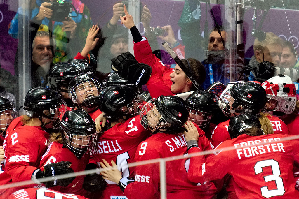 Description of . Team Switzerland celebrates their 4-3 win over Sweden in the women's ice hockey bronze medal game at Bolshoy Arena at the 2014 Winter Olympics, Thursday, Feb. 20, 2014, in Sochi, Russia. (AP Photo/J. David Ake)
