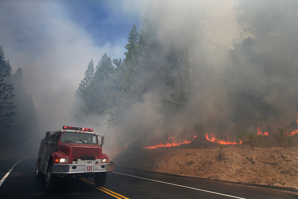 Description of . A fire truck drives past burning trees as firefighters continue to battle the Rim Fire near Yosemite National Park, Calif., on Monday, Aug. 26, 2013. Crews working to contain one of California's largest-ever wildfires gained some ground Monday against the flames threatening San Francisco's water supply, several towns near Yosemite National Park and historic giant sequoias. (AP Photo/Jae C. Hong)
