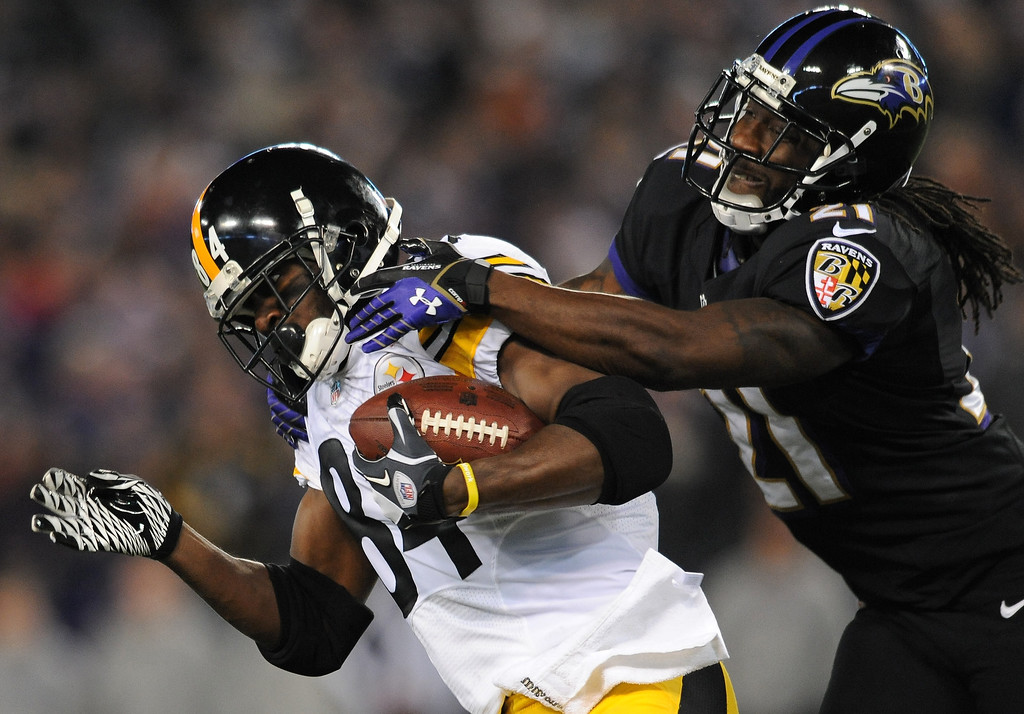 Description of . Pittsburgh Steelers wide receiver Antonio Brown, left, is tackled by Baltimore Ravens cornerback Lardarius Webb after getting a first down in the first half of an NFL football game on Thursday, Nov. 28, 2013, in Baltimore. (AP Photo/Gail Burton)
