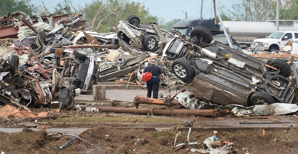 . A rescue worker looks for victims in the Moore Hospital parking lot after being hit by a tornado that destroyed buildings and overturned cars in Moore, Oklahoma, near Oklahoma City, May 20, 2013.  A huge tornado with winds of up to 200 miles per hour (320 kph) devastated the Oklahoma City suburb of Moore on Monday, ripping up at least two elementary schools and a hospital and leaving a wake of tangled wreckage. At least four people were killed, KFOR television said, citing a reporter\'s eyewitness account, and hospitals said dozens of people were injured. REUTERS/Gene Blevins