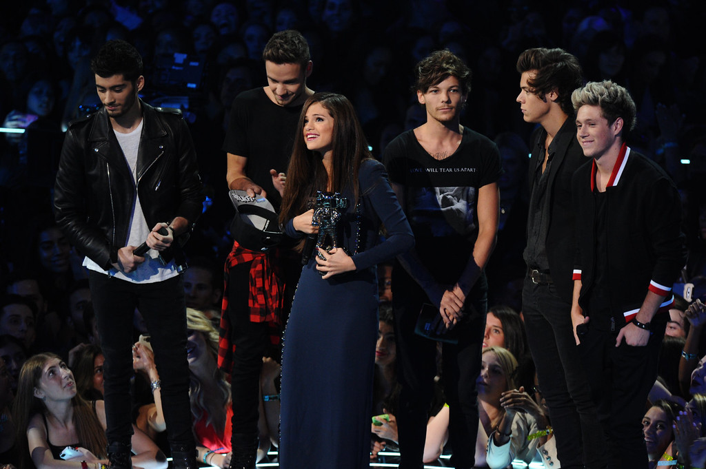 Description of . Zayn Malik, background from left, Liam Payne, Louis Tomlinson, Niall Horan and Harry Styles of One Direction present the award for best pop video for