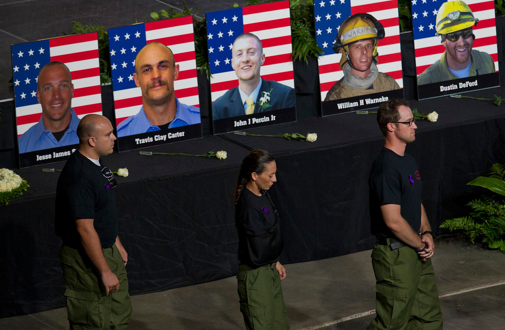 Description of . Former Granite Mountain Hotshot firefighters walk past photos of their fallen comrades during a memorial service for Yarnell firefighters at Tim's Toyota Center in Prescott Valley, Arizona July 9, 2013.   REUTERS/Michael Chow/Pool