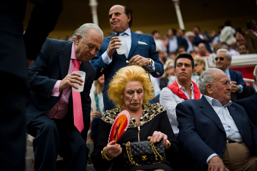 Description of . In this May 17, 2012 file photo, people sit before a bullfight of the San Isidro Fair, in Madrid, Spain.  This photo is one in a series of images by Associated Press photographer Daniel Ochoa de Olza that won the second place prize for the Observed Portrait series category in the World Press Photo 2013 photo contest. (AP Photo/Daniel Ochoa de Olza, File)