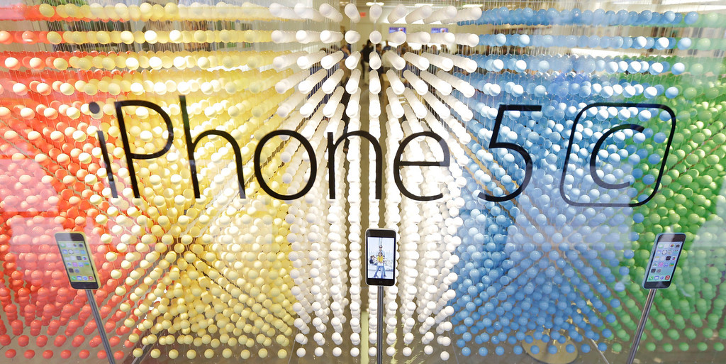 Description of . A display of iPhone 5C's at an Apple store during the opening day of sale of the new phones in Richmond, Va., Friday, Sept. 20, 2013.  (AP Photo/Steve Helber)
