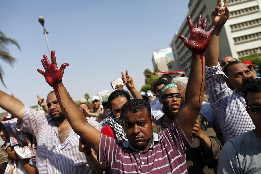 Description of . A supporter of the Muslim Brotherhood and ousted Egyptian president Mohamed Morsi raises his hands covered in the blood of victims who were shot during a gun battle outside the Cairo headquarters of the Republican Guard on July 5, 2013. At least three supporters of Morsi were killed and many others were wounded as they gathered for a protest, an AFP correspondent said. Shooting could be heard coming from both the Republican Guard and the ranks of the protesters. MAHMOUD KHALED/AFP/Getty Images