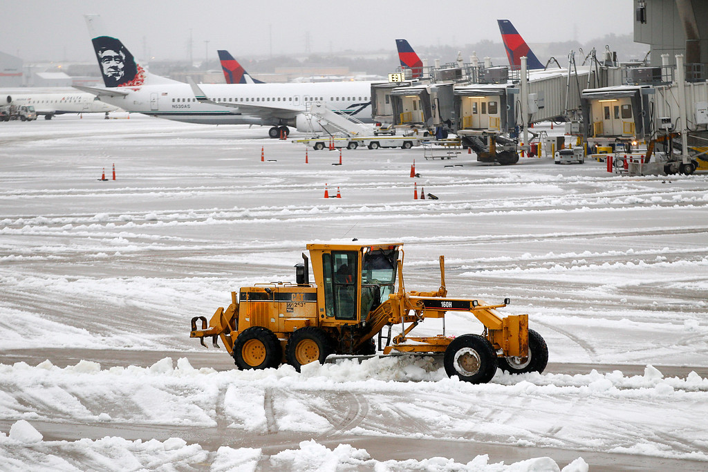 Description of . Snow removal equipment clears the wet sleet on the ramp area at Dallas-Fort Worth International Airport, Friday, Dec. 6, 2013.  The weather forced more than 1,000 cancellations at Dallas-Fort Worth International Airport, one of the nation's busiest airports and a key hub for Fort Worth-based American Airlines. Many travelers were stuck waiting and hoping for another flight to take them to their destination.  (AP Photo/The Dallas Morning News, Tom Fox)