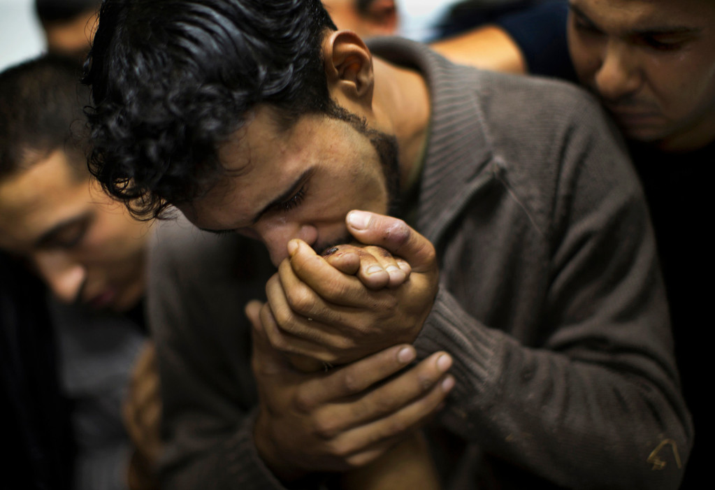 Description of . In this Nov. 18, 2012 file photo, a Palestinian man kisses the hand of a dead relative in the morgue of Shifa Hospital in Gaza City. This photo was one in a series of images by Associated Press photographer Bernat Armangue that won the first place prize in the World Press Photo 2013 photo contest for the Spot News series category.  (AP Photo/Bernat Armangue, File)