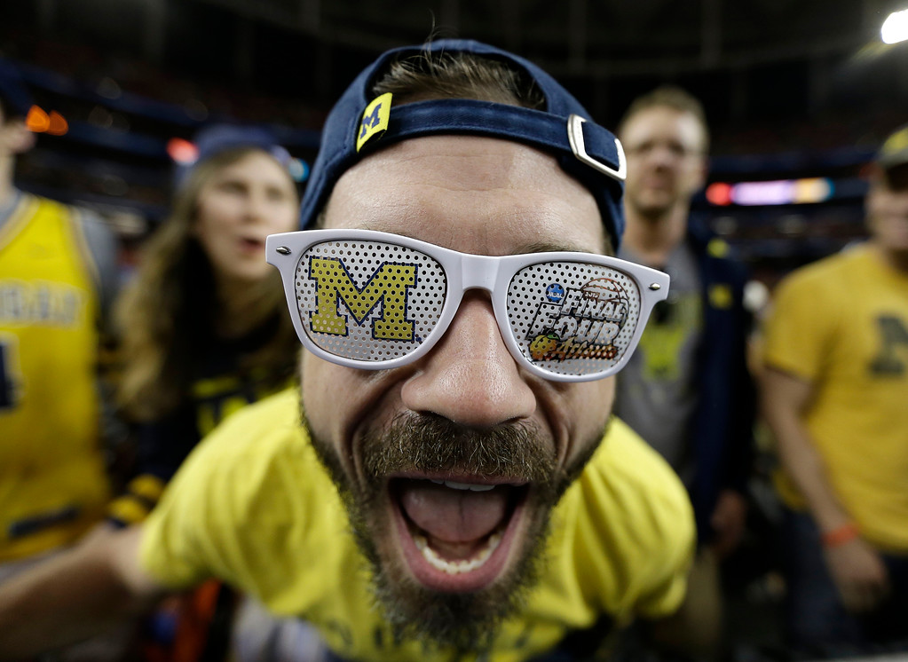 Description of . Michigan student Aaron Ruhlig cheers before the first half of the NCAA Final Four tournament college basketball semifinal game against Syracuse, Saturday, April 6, 2013, in Atlanta. (AP Photo/Charlie Neibergall)