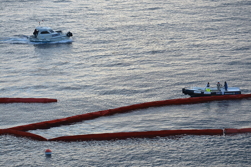 Description of . Small boats pass close to anti-pollution floating barriers settled around the wreck of Italy's Costa Concordia cruise ship, on September 16, 2013. Salvage workers attempt to raise the cruise ship today in the largest and most expensive maritime salvage operation in history, so-called