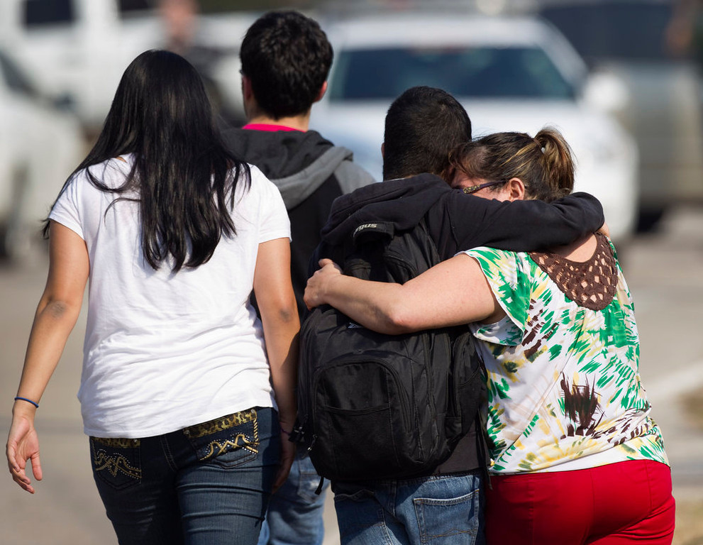 Description of . A woman, right, embraces a Lone Star College student after he was evacuated from the campus following a shooting at the north Harris County school Tuesday, Jan. 22, 2013, in Houston. The shooting wounded three people Tuesday and sent students fleeing for safety as officials placed the campus on lockdown, officials said. (AP Photo/Houston Chronicle, Brett Coomer)