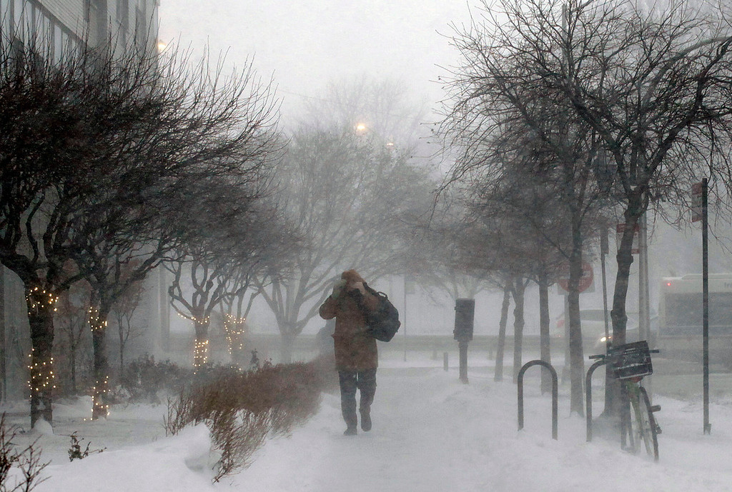 Description of . A morning commuter walks against blowing snow Thursday, Jan. 2, 2014, in Chicago. As much as a foot of snow or more was forecast for some areas in the Northeast overnight Thursday into Friday, and temperatures were expected to plummet, with some areas seeing highs just above zero, according to the National Weather Service. (AP Photo/Kiichiro Sato)