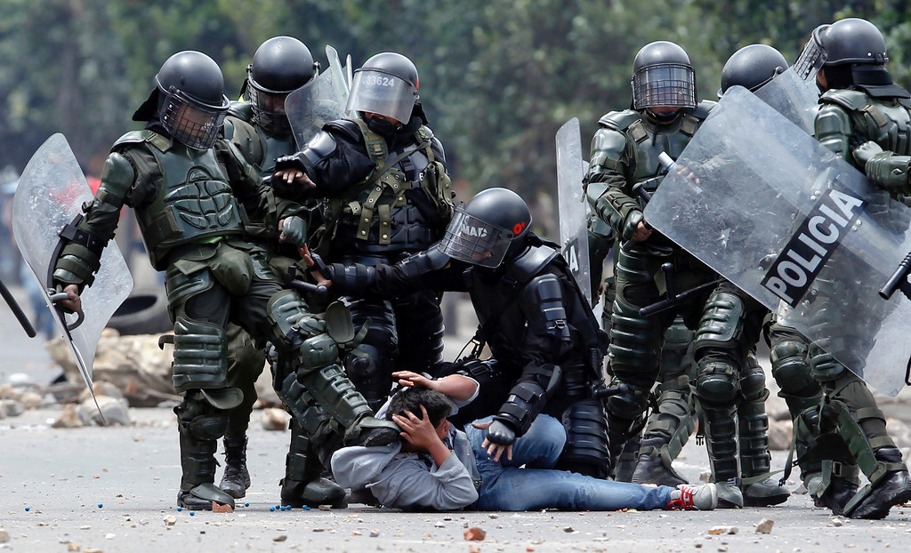 Description of . A riot police officer, left, kicks a protester as another, center, tries to protect him before his arrest during protests in Ubate, north of Bogota, Colombia, Monday, Aug. 26, 2013.  Hundreds of protesters clashed with police in support of farmers who have being blockading Colombian highways for a week for an assortment of demands that include reduced gasoline prices, increased subsidies and the cancellation of free trade agreements. (AP Photo/Fernando Vergara)