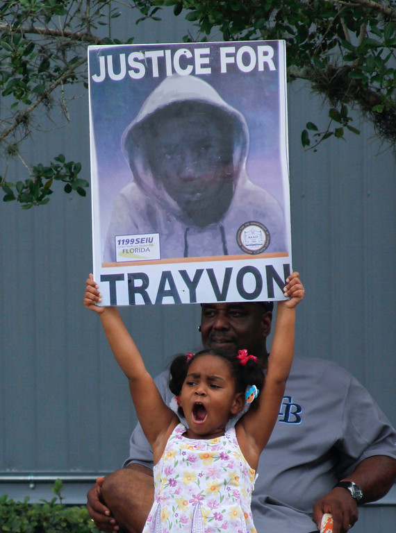 Description of . Hanna Brianna, 5, holds a sign in front of her home in the Goldsboro Historical neighborhood, Saturday, July 13, 2013, in Sanford, Fla. while residents wait for word on the verdict in the George Zimmerman trial. Zimmerman is charged with the 2012 shooting death of Trayvon Martin. (AP Photo/Mike Brown)