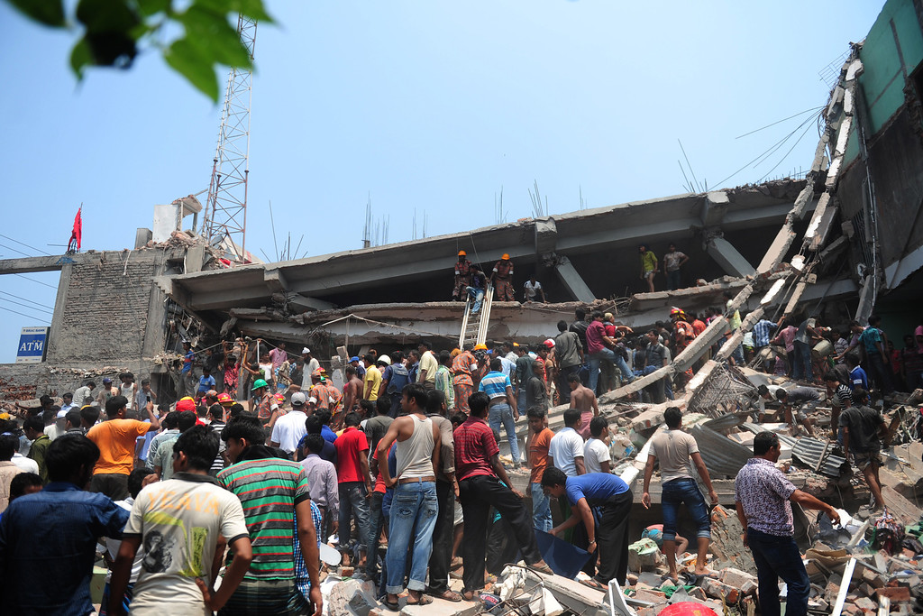 Description of . Bangladeshi Army personnel and civilian volunteers work on the scene after an eight-story building collapsed in Savar, on the outskirts of Dhaka, on April 24, 2013.  AFP PHOTO/Munir uz ZAMAN/AFP/Getty Images
