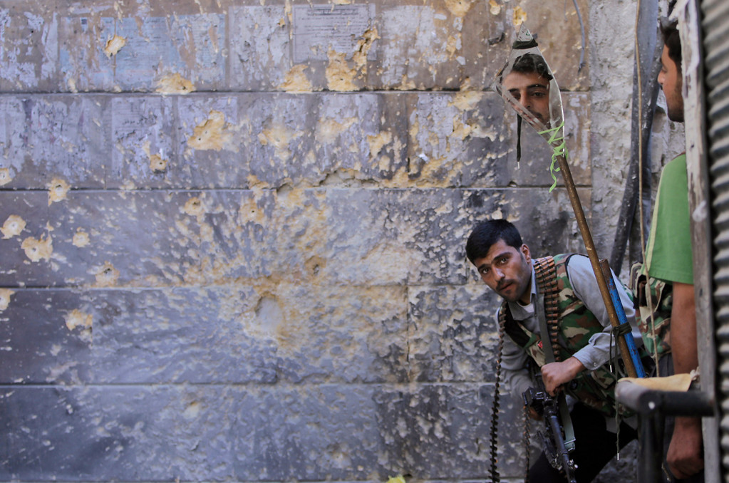 Description of . FILE - A Free Syrian Army soldier, right, looks through a mirror that helps him see Syrian troops from the other side, as he takes his position with his comrade during fighting, at the old city of Aleppo city, Syria, Monday, Sept. 24, 2012. (AP Photo/Hussein Malla, File)