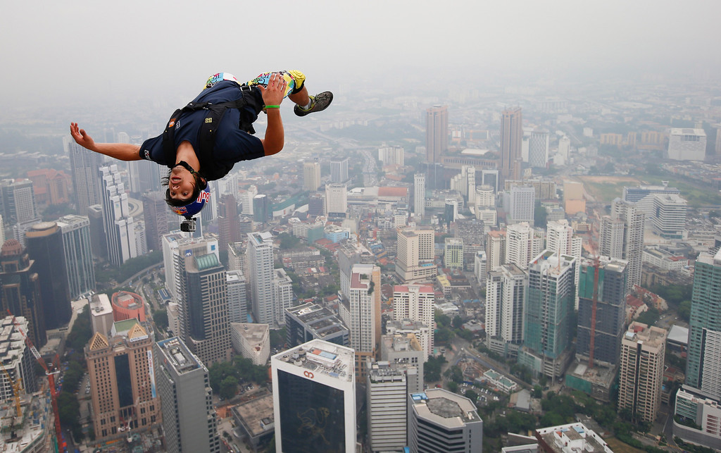 Description of . Base jumper Vincent Philippe Benjamin Reffet of France leaps from the 300-meter Open Deck of the Malaysia's landmark, Kuala Lumpur Tower during the International Tower Jump in Kuala Lumpur, Friday, Sept. 27, 2013.  (AP Photo/Vincent Thian)