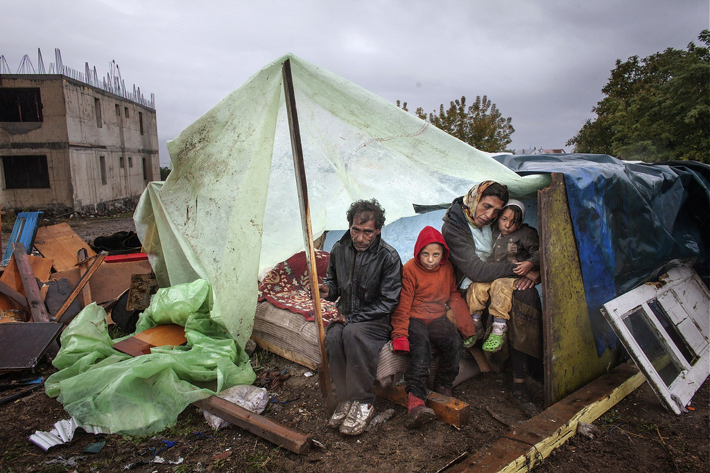 Description of . A Roma family of Turkish origin sits under an improvised shelter during heavy rain in Eforie Sud, Romania, on September 30, 2013 before an announcement by the Mayor on their case. Romanian authorities evicted around 100 Roma from a town near the Black Sea coast without providing them with alternative housing, prompting criticism from Amnesty International. The Roma families spent three days in a nearby field despite the cold weather until the mayor decided on September 30, 2013 to host them in an old school.