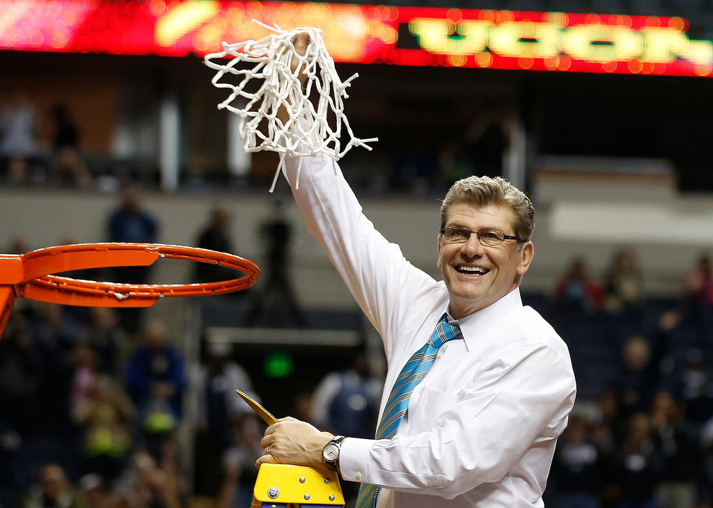 Description of . Connecticut head coach Geno Auriemma holds the net after the second half of the championship game against Notre Dame in the Final Four of the NCAA women's college basketball tournament, Tuesday, April 8, 2014, in Nashville, Tenn. Connecticut won 79-58. (AP Photo/John Bazemore)