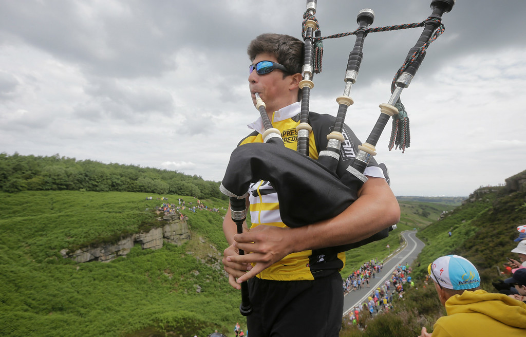 Description of . A bag piper plays as spectators wait for the pack to pass during the second stage of the Tour de France cycling race over 201 kilometers (124.9 miles) with start in York and finish in Sheffield, England, Sunday, July 6, 2014. (AP Photo/Laurent Cipriani)