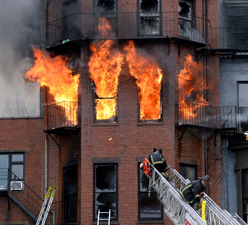 Description of . Boston firefighters work a multi-alarm brownstone fire, Wednesday, March 26, 2014, in Boston. A Boston city councilor said two firefighters have died in a fire that ripped through the brownstone. (AP Photo/The Boston Herald, Christopher Evans)
