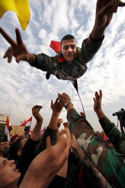 Description of . FILE - A Syrian solider flashes the victory sign as he is thrown in the air during a rally at Umayyad Square in Damascus, Syria, Wednesday, Dec. 21, 2011. (AP Photo/ Muzaffar Salman, File)
