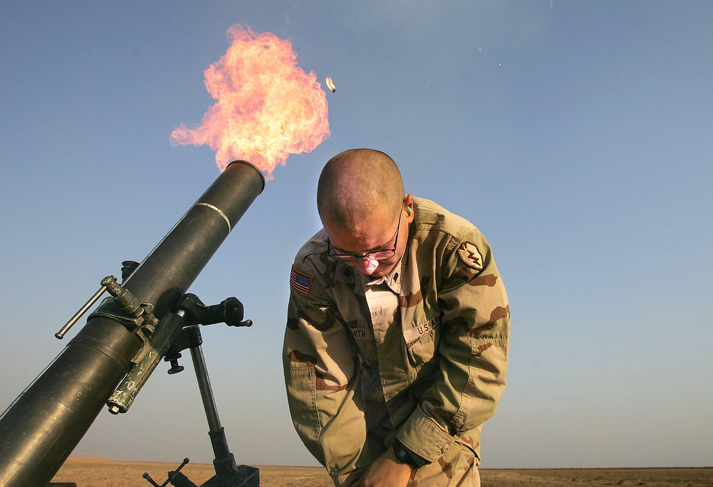 ". Spc. Franklin Smith pulls away as a 120mm mortar blasts out of a tube January 17, 2005 at the edge of the US airbase in Tal Afar, Iraq. US mortaring teams frequently fire ""harassment and interdiction\"" mortar fusillades from the base to suspected enemy positions or watched areas nearby. (Photo by Chris Hondros/Getty Images)"