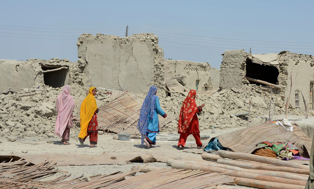 Description of . Pakistani earthquake survivors walk past collapsed mud houses at Labach area, in the earthquake-devastated district of Awaran on September 26, 2013.  AFP PHOTO / Banaras KHAN/AFP/Getty Images