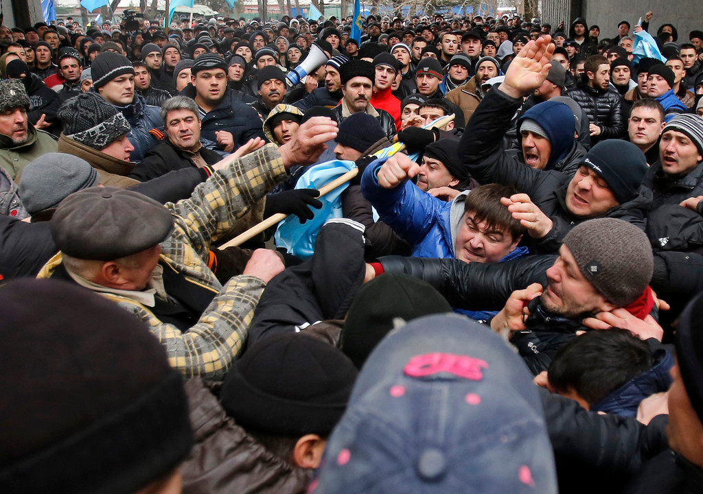 Description of . Pro-Russian protesters, right, clash with Crimean Tatars in front of a local government building in Simferopol, Crimea, Ukraine, Wednesday, Feb. 26, 2014. More than 10,000 Muslim Tatars rallied in support of the interim government. That group clashed with a smaller pro-Russian rally nearby. Fistfights broke out between pro- and anti-Russian demonstrators in Ukraine's strategic Crimea region on Wednesday as Russian President Vladimir Putin ordered massive military exercises just across the border. (AP Photo/Darko Vojinovic)