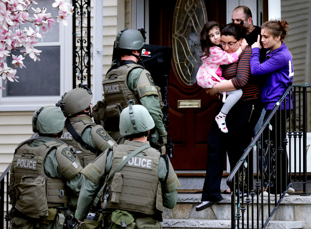 Description of . A woman carries a girl from their home as a SWAT team searching for a suspect in the Boston Marathon bombings enters the building in Watertown, Mass., Friday, April 19, 2013. Two suspects in the Boston Marathon bombing killed an MIT police officer, injured a transit officer in a firefight and threw explosive devices at police during their getaway attempt in a long night of violence that left one of them dead and another still at large Friday, authorities said as the manhunt intensified for a young man described as a dangerous terrorist. (AP Photo/Charles Krupa)
