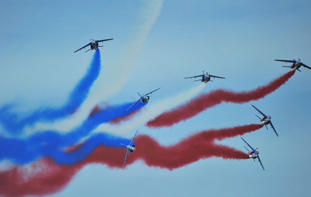 Description of . Alpha jets, part of the Patrouille Acrobatique de France, leave trails of smoke in the colours of the French national flag during an international D-Day commemoration ceremony on the beach of Ouistreham, Normandy, on June 6, 2014, marking the 70th anniversary of the World War II Allied landings in Normandy.  AFP PHOTO / GUILLAUME  SOUVANT/AFP/Getty Images