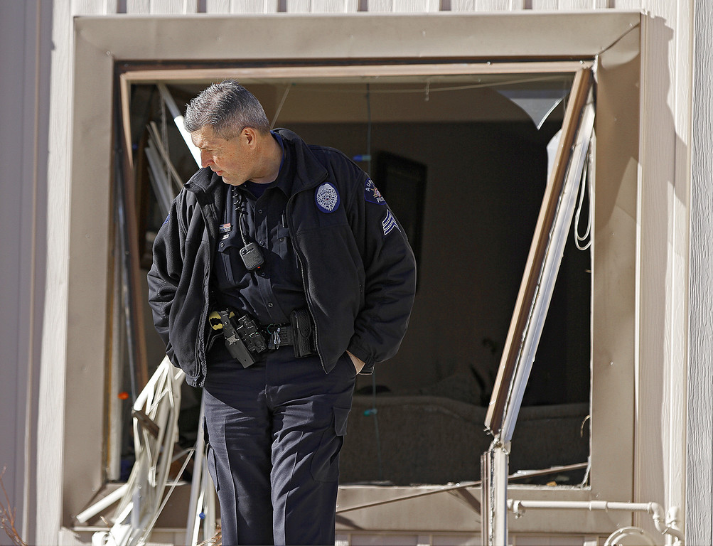 Description of . A police officer stands watch in front of a broken out window in a town home where four people were killed Saturday morning including the gunman who held police at bay for several hours at the complex January 5, 2013 in Aurora, Colorado. Aurora SWAT team members shot a gunman after he went to a second-floor window and fired at police. The gunman also allegedly fatally shot two men and a woman that he had taken hostage. One woman managed to escape from an upstairs back window, ran from the home and called police just before 3 a.m., said Cassidee Carlson, Aurora police spokeswoman.  (Photo by Marc Piscotty/Getty Images)